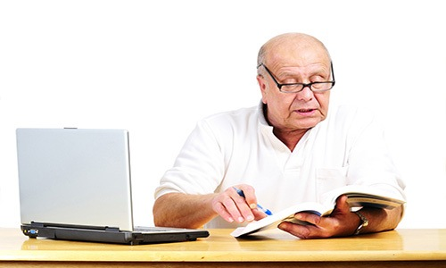 An elderly man working on some paers and his laptop